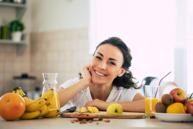 Jolie jeune femme brune belle et heureuse dans la cuisine à la maison