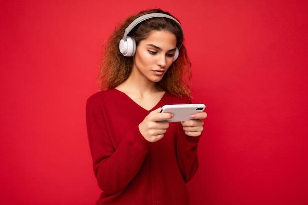 Jolie jeune femme brune bouclée concentrée portant un pull rouge foncé isolé sur fond rouge