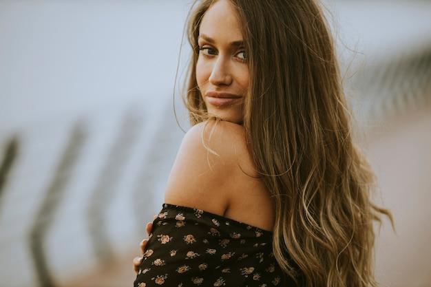 Jolie jeune femme brune cheveux longs marchant au bord de la rivière