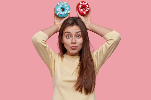 Jolie jeune femme brune drôle tient deux délicieux beignets, vêtus de vêtements jaunes, modèles sur espace rose