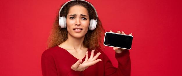 Jolie jeune femme brune frisée insatisfaite et choquée portant un pull rouge foncé isolé sur rouge