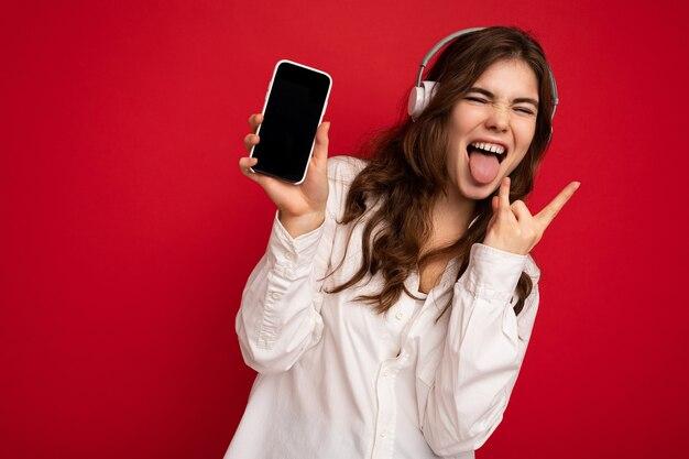Jolie jeune femme brune frisée positive folle portant une chemise blanche isolée sur fond rouge