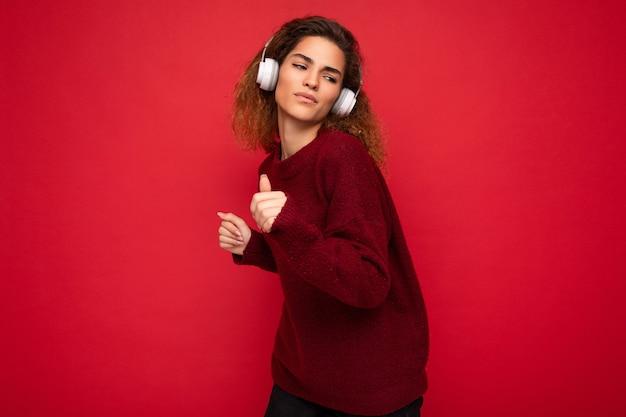 Jolie jeune femme brune frisée positive portant un pull rouge foncé isolé sur fond rouge