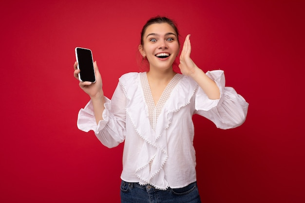Jolie jeune femme brune heureuse portant un chemisier blanc isolé sur fond rouge