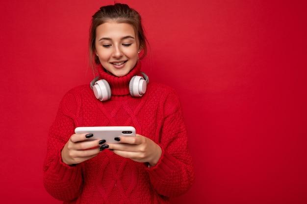 Jolie jeune femme brune heureuse portant un pull rouge isolé sur un mur de fond rouge tenant et utilisant un téléphone portable en surfant sur internet et portant des écouteurs bluetooth regardant un smartphone.