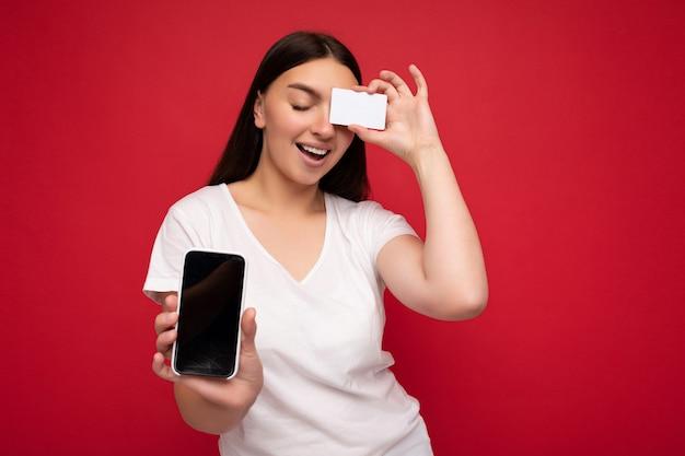 Jolie jeune femme brune heureuse portant un t-shirt blanc décontracté isolé sur fond rouge avec