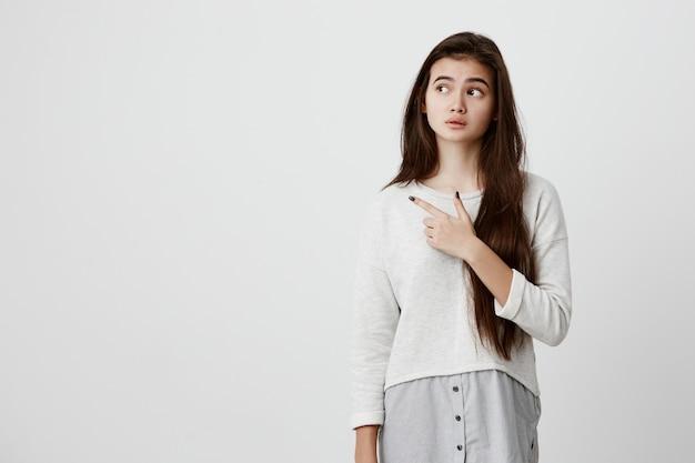 Jolie jeune femme brune joyeuse pointant avec l'index loin, montrant quelque chose d'intéressant et d'excitant