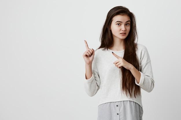 Jolie jeune femme brune joyeuse pointant les index, montrant quelque chose d'intéressant et d'excitant