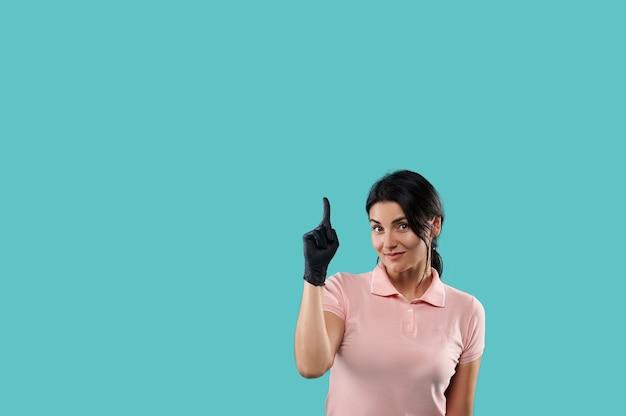 Jolie jeune femme brune portant un polo rose et un gant en latex noir pointant son index vers le haut sur un fond bleu avec espace de copie