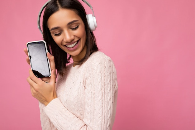 Jolie jeune femme brune portant un pull décontracté rose isolé sur un mur de fond rose portant