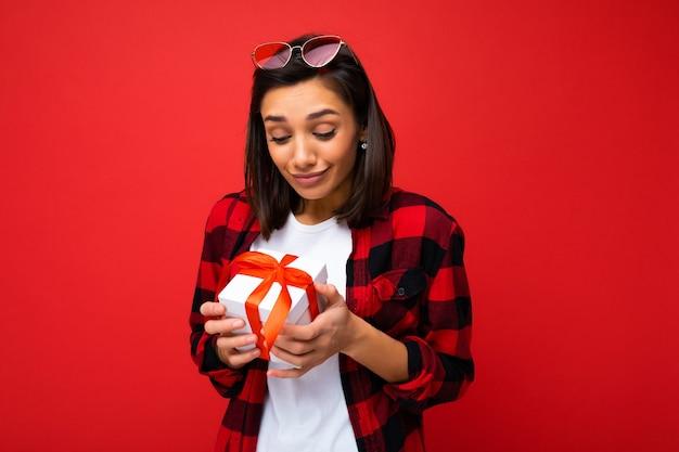 Jolie jeune femme brune positive isolée sur un mur rouge portant un t-shirt décontracté blanc et une chemise rouge et noire tenant une boîte cadeau blanche avec un ruban rouge et à la recherche au présent.