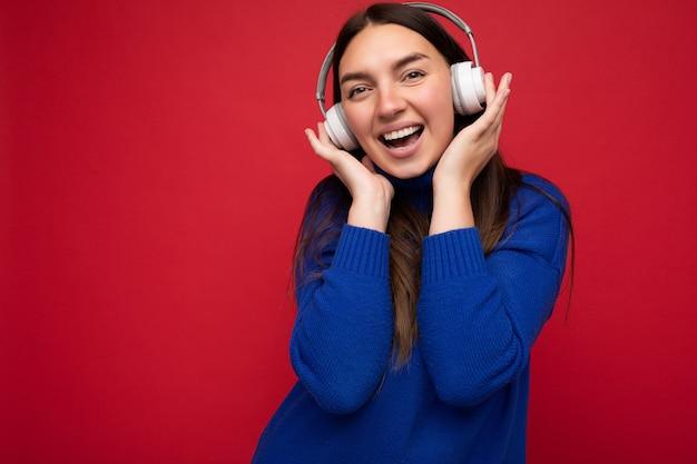 Jolie jeune femme brune positive portant un pull bleu isolé