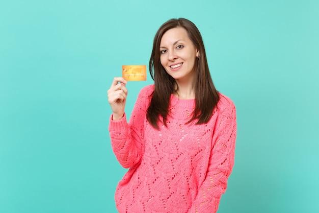 Jolie jeune femme brune en pull rose tricoté à la recherche de caméra tenant en main une carte de crédit isolée sur fond de mur turquoise bleu portrait en studio. concept de mode de vie des gens. maquette de l'espace de copie.