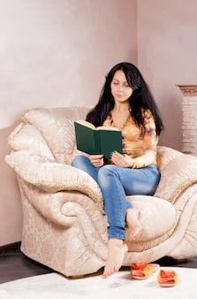 Jolie jeune femme brune recroquevillée dans un confortable fauteuil rembourré crème lisant un livre avec son slip sur des chaussures allongé sur le tapis à côté d'elle