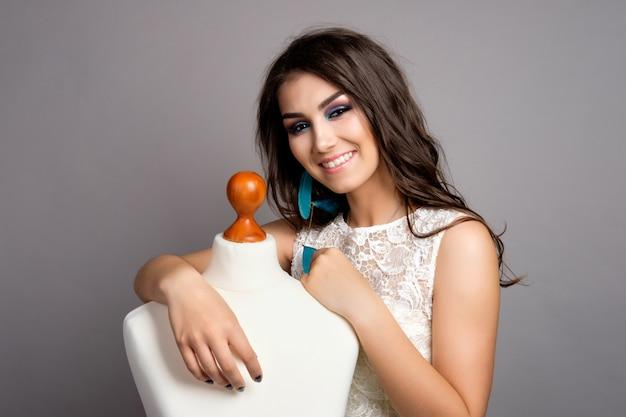 Jolie jeune femme brune en robe blanche hugging dummy, studio smiling portrait sur fond gris, smiling bride portrait
