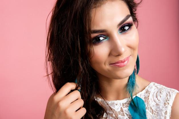 Jolie jeune femme brune en robe blanche studio smiling portrait sur fond rose