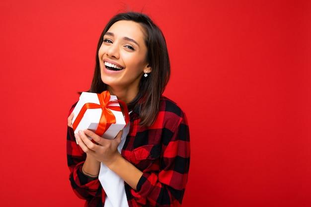 Jolie jeune femme brune souriante positive isolée sur un mur coloré portant une tenue à la mode tous les jours tenant une boîte-cadeau