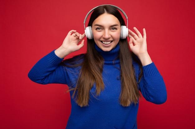Jolie jeune femme brune souriante et positive portant un pull bleu isolé sur un mur de fond rouge portant des écouteurs bluetooth blancs écoutant de la musique cool et s'amusant en regardant la caméra