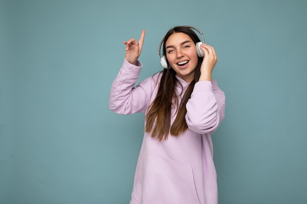 Jolie jeune femme brune souriante et positive portant un sweat à capuche violet clair isolé sur bleu