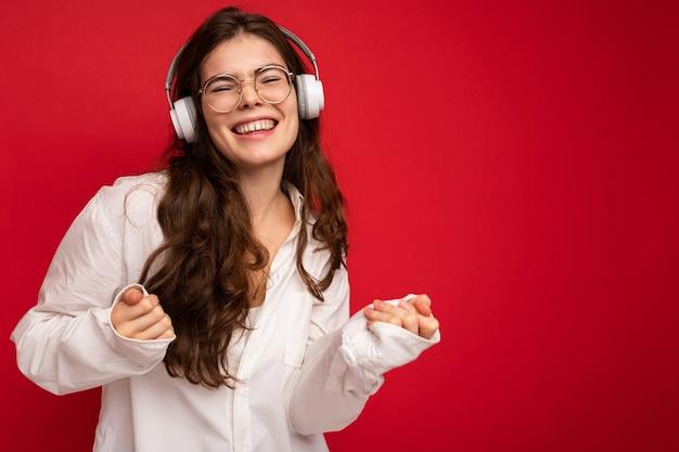 Jolie jeune femme brune souriante et souriante portant une chemise blanche et des lunettes optiques isolées sur fond rouge portant des écouteurs bluetooth sans fil blancs écoutant de la musique et dansant