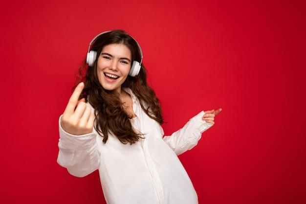 Jolie jeune femme brune souriante et souriante portant une chemise blanche et des lunettes optiques