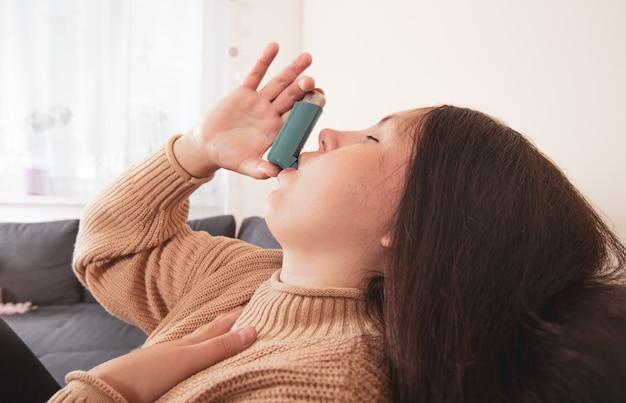 Jolie jeune femme brune utilisant un inhalateur pour l'asthme lors d'une forte crise d'asthme le produit pharmaceutique est utilisé pour prévenir et traiter la respiration sifflante