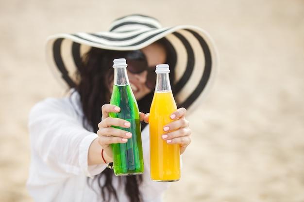 Jolie jeune femme buvant un cocktail sur la plage. jolie fille offrant un verre. belle femme buvant de la limonade