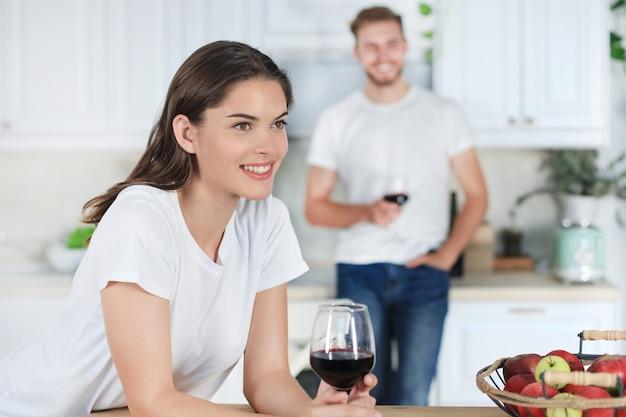 Jolie jeune femme buvant du vin à la maison dans la cuisine.