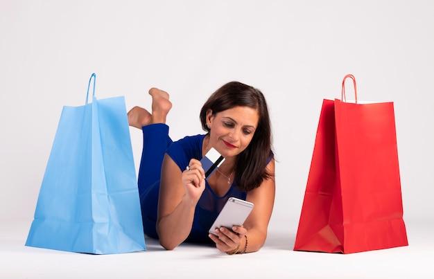 Jolie jeune femme caucasienne allongée sur le sol en regardant le téléphone portable et en utilisant la carte de crédit