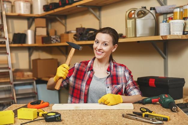 Jolie jeune femme caucasienne aux cheveux bruns en chemise à carreaux, t-shirt gris, gants jaunes travaillant dans un atelier de menuiserie sur une table en bois avec différents outils, martelant des clous dans une planche avec un marteau.