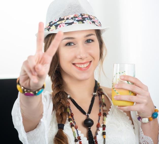 Jolie jeune femme avec un chapeau d'été boit un verre de jus d'orange