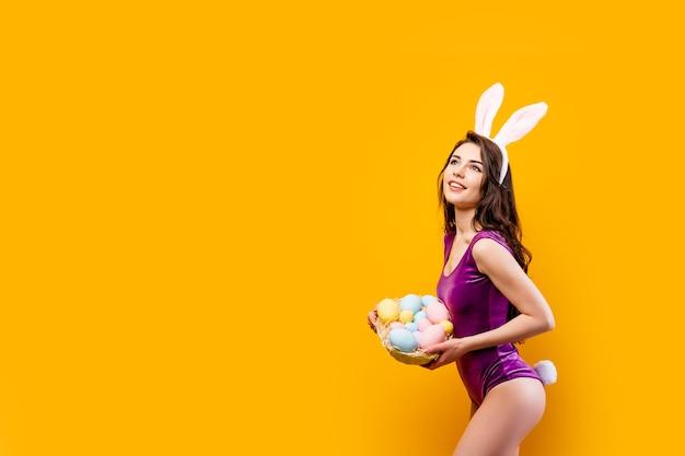 Jolie jeune femme chaude portant un body et des oreilles de lapin tenant un panier avec des oeufs de pâques colorés tout en posant sur le mur jaune.