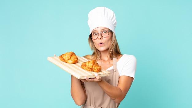 Jolie jeune femme chef blonde tenant un plateau de croissants