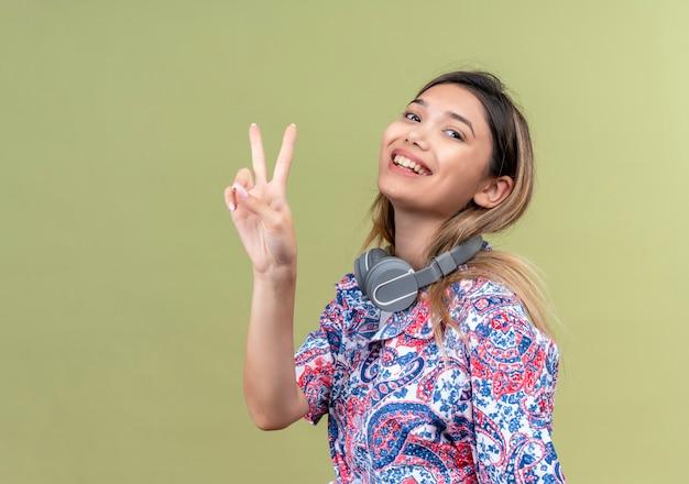 Une jolie jeune femme en chemise imprimée paisley portant des écouteurs en souriant tout en montrant le geste de deux mains sur un mur vert