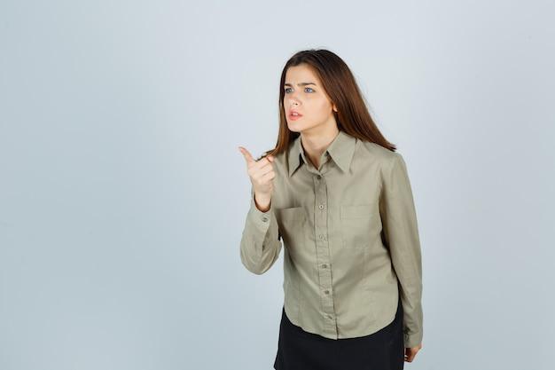 Jolie jeune femme en chemise, jupe avertissant avec le doigt et semblant furieuse, vue de face.