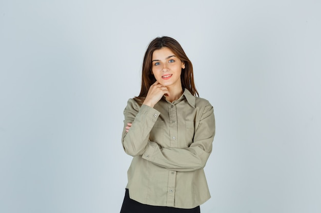 Jolie jeune femme en chemise, jupe debout dans une pose de réflexion et regardant joyeusement, vue de face.