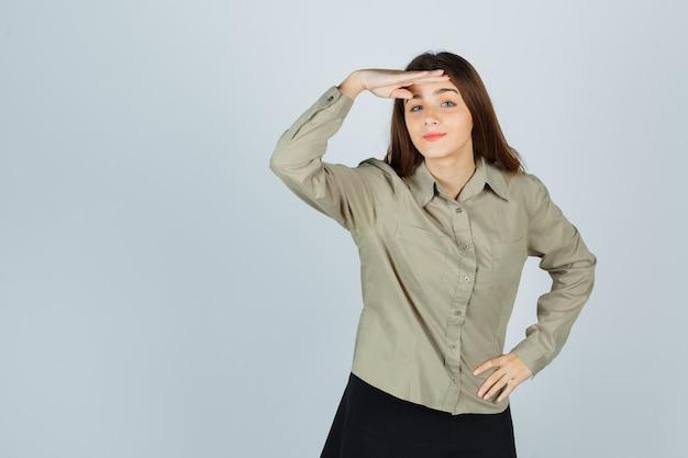 Jolie jeune femme en chemise, jupe tenant la main sur la tête et l'air curieux, vue de face.