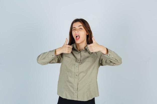 Jolie jeune femme en chemise montrant le double pouce vers le haut tout en clignant des yeux et en ayant l'air confiant, vue de face.