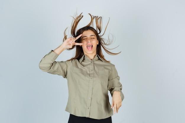 Jolie jeune femme en chemise montrant le signe v près de l'œil, tirant la langue tout en posant avec des cheveux volants et l'air énergique, vue de face.