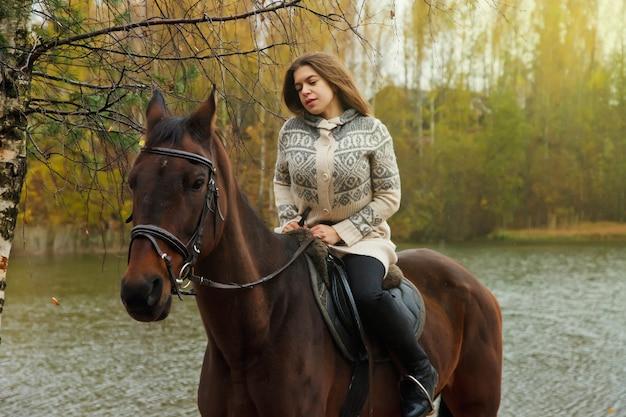 Jolie jeune femme à cheval dans la forêt d'automne au bord du lac. la femelle du cavalier conduit son cheval dans le parc par mauvais temps nuageux avec de la pluie. concept d'équitation en plein air, de sports et de loisirs. espace de copie