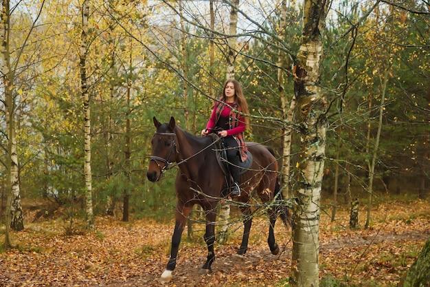 Jolie jeune femme à cheval dans la forêt d'automne sur route de campagne. la femelle du cavalier conduit son cheval dans le parc par mauvais temps nuageux avec pluie. concept d'équitation en plein air, de sports et de loisirs. espace de copie