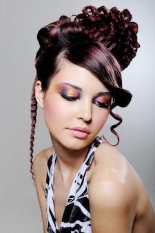 Jolie jeune femme avec une coiffure créative de mode et un fard à paupières multicolore lumineux