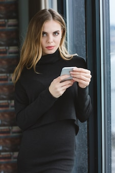 Jolie jeune femme confiante utilisant un téléphone portable debout près de la fenêtre