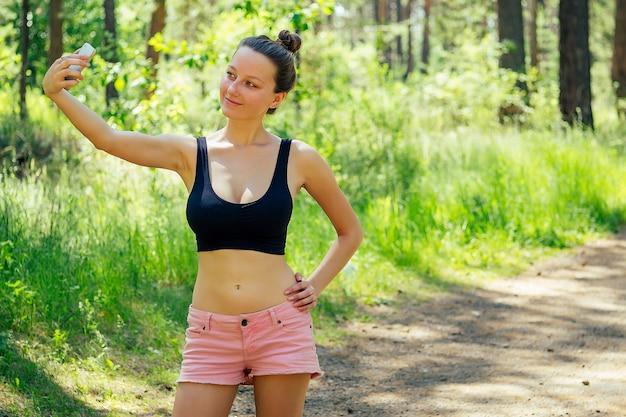 Jolie jeune femme de coureur sexy brune mince athlétique en short rose court et haut noir faisant selfie téléphone r dans le parc