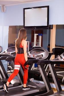 Une jolie jeune femme court sur un tapis roulant, est engagée dans un club de fitness