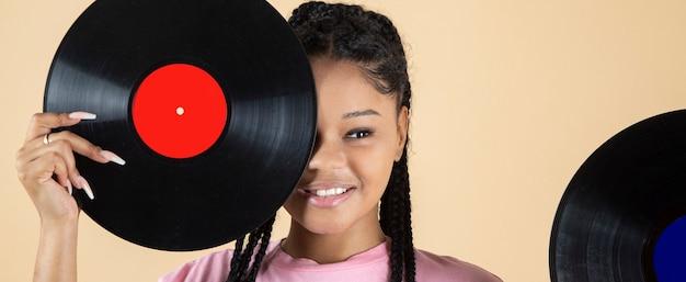 Jolie jeune femme couvrant son œil avec un vinyle musical classique