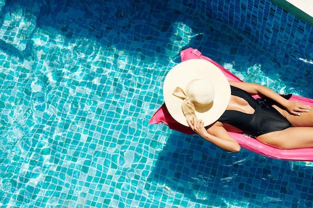 Jolie jeune femme couvrant le visage avec un chapeau de paille lors d'un bain de soleil sur un matelas flottant dans la piscine