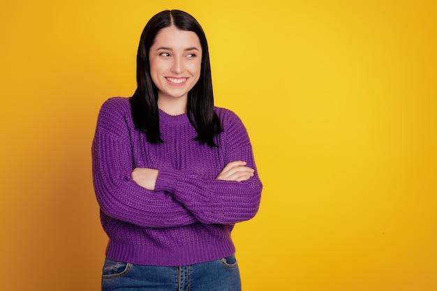 Jolie jeune femme a croisé les bras debout sur fond jaune curieux look espace vide. pose confiante