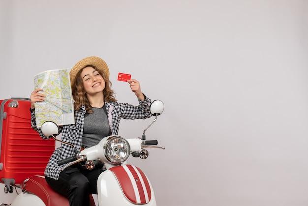Jolie jeune femme sur cyclomoteur tenant une carte et une carte sur fond gris