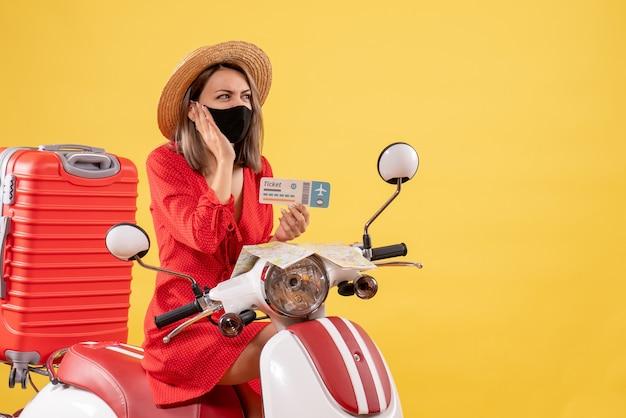 Jolie jeune femme sur cyclomoteur avec valise rouge tenant un ticket